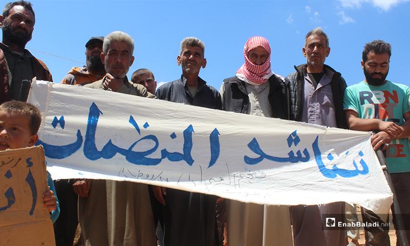 """نازحو مخيم """"العمران"""" غربي حربنوش يرفعون لافتة """"نناشد المنظمات"""" خلال مظاهرتهم المطالبة بتوفيرالغذاء والماء والخبز والخدمات- 10 من أيار (عنب بلدي)"""