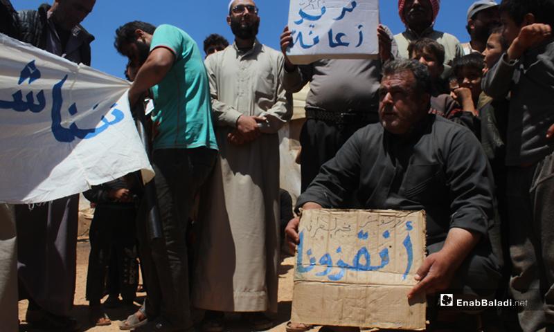 """نازحو مخيم """"العمران"""" غربي حربنوش، يرفعون لافتات خلال مظاهرتهم مطالبين بتوفير الحاجات الأساسية والخدمات- 10 من أيار (عنب بلدي)"""