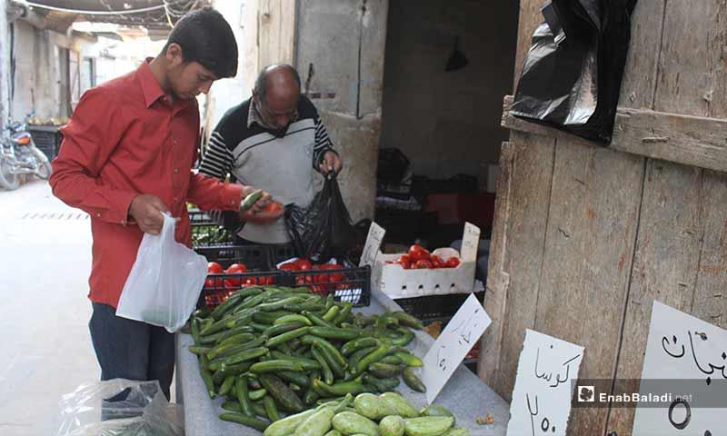رجلان يشتريان الخضروات في بلدة سرمين بريف إدلب الشرقي قبل الإفطار- 8 من أيار (عنب بلدي)
