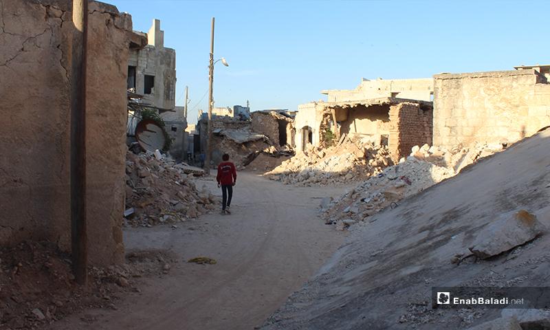 طفل يسير وحيدًا بين ركام المنازل المهدمة في بلدة سرمين بريف إدلب الشرقي- 8 من أيار (عنب بلدي)