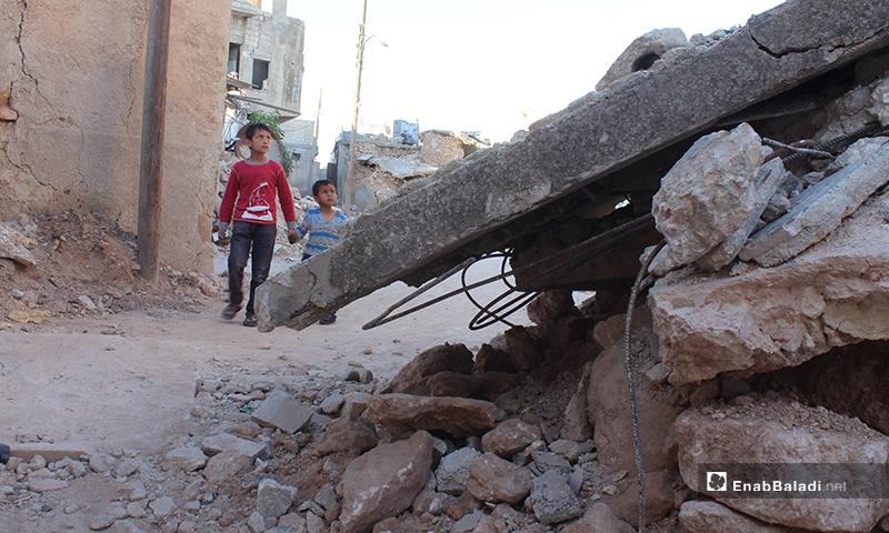 طفلان يسيران إلى جانب منزل مهدم في بلدة سرمين بريف إدلب الشرقي- 8 من أيار (عنب بلدي)