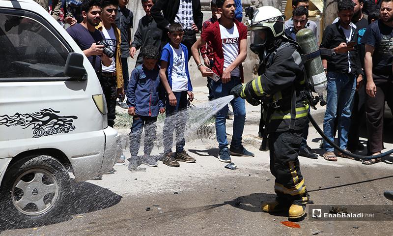 عنصر من الدفاع المدني والأهالي في مكان انفجار السيارة التابعة لعنصر من فصيل السلطان مراد في مدينة الباب- 25 من أيار (عاصم الملحم/ عنب بلدي)