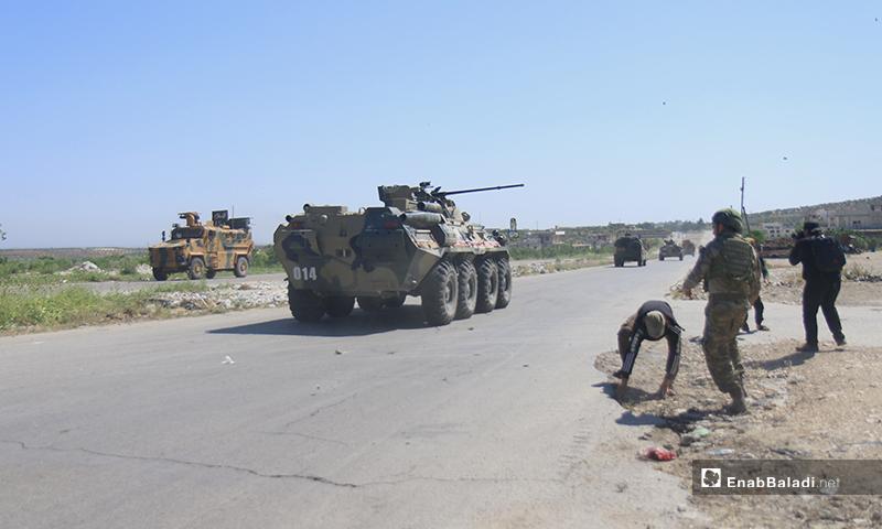 مدني في إدلب يحمل الحجارة ليرجم بها الآلية الروسية العسكرية خلال الدورية المشتركة مع تركيا- 14 من أيار (عنب بلدي)