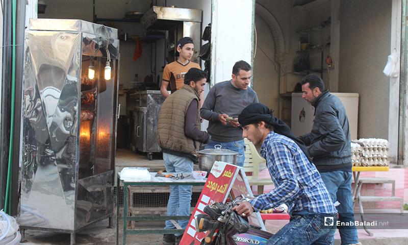أشخاص يشترون الدجاج المشوي قبل الإفطار من مطعم في بلدة سرمين بريف الشرقي- 8 من أيار (عنب بلدي)