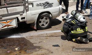 عنصر من الدفاع المدني والأهالي في مكان انفجار السيارة التابعة لعنصر من فصيل السلطان مراد في مدينة الباب- 25 من أيار (عاصم ملحم/ عنب بلدي)