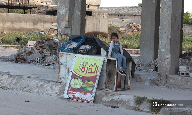 """طفلة تبيع الخبز في بسطتها وأمامها شارة المحل """"أفران الدرة"""" في بلدة سرمين بريف إدلب الشرقي- 8 من أيار (عنب بلدي)"""