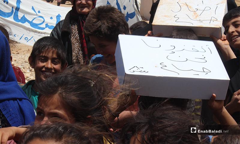 """طفل يحمل صندوق كتب عليه """"أنقذونا نحن جياع"""" خلال مظاهرة نازحو مخيم """"العمران"""" غربي حربنوش- 10 من أيار (عنب بلدي)"""