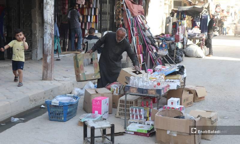 بائع يرتب بضاعته في شارع وسط مدينة الرقة 12  من أيار 2020 (عنب بلدي)