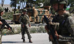 عناصر من الجيش التركي بجوار عربة عسكرية ينتشرون على الطريق الدولي حلب اللاذقية خلال تسيير الدورية المشتركة الحادية عشر - 14 أيار 2020 (عنب بلدي/ يوسف غريبي)