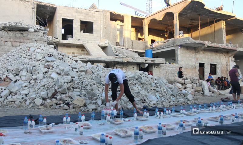 شاب يضع الطعام والماء على المائدة من أجل الإفطار الجماعي في مدينة الأتارب وآثار الدمار من حوله- 8 من أيار (عنب بلدي)
