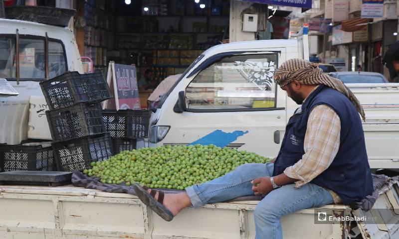 """بائع خوخ أخضر """"جارنك"""" وسط شارع مزدحم في مدينة الرقة 12  من أيار 2020 (عنب بلدي)"""