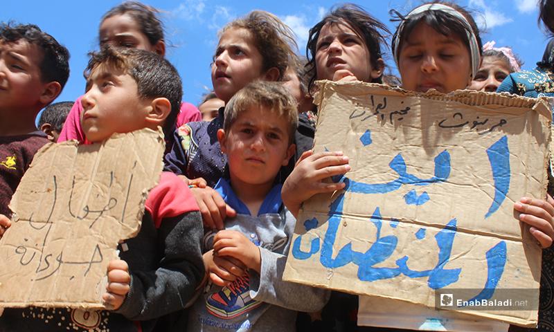 """أطفال يحملون لافتات كتب عليها """"أين المنظمات""""، و""""أطفال جوعانة"""" خلال مظاهرة مخيم """"العمران"""" غربي حربنوش- 10 من أيار (عنب بلدي)"""