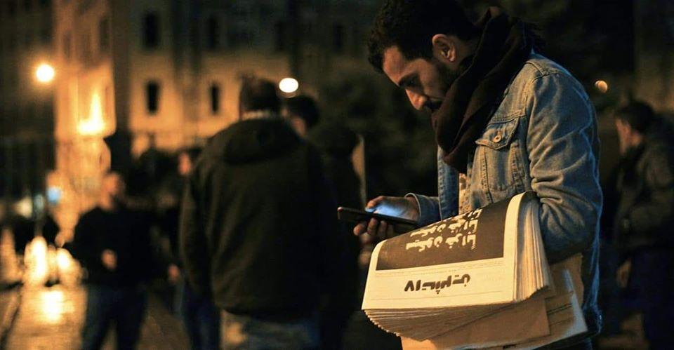 """بشير أبو زيد حاملًا صحيفة """"17 تشرين"""" في لبنان (صفحة بشير في فيس بوك)"""