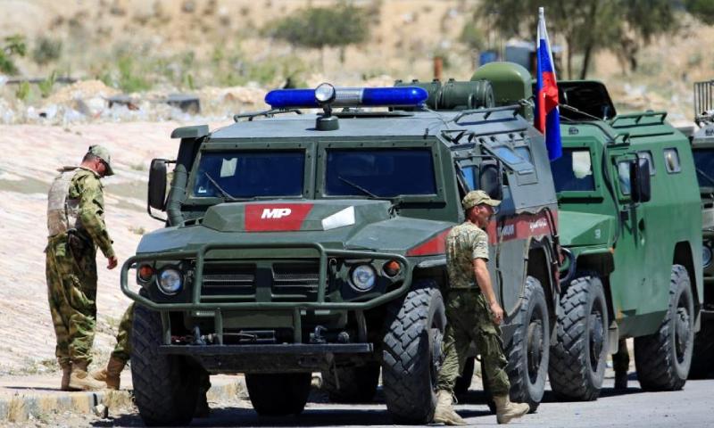 جنود روس بجانب عربات عسكرية روسية في سوريا (رويترز)