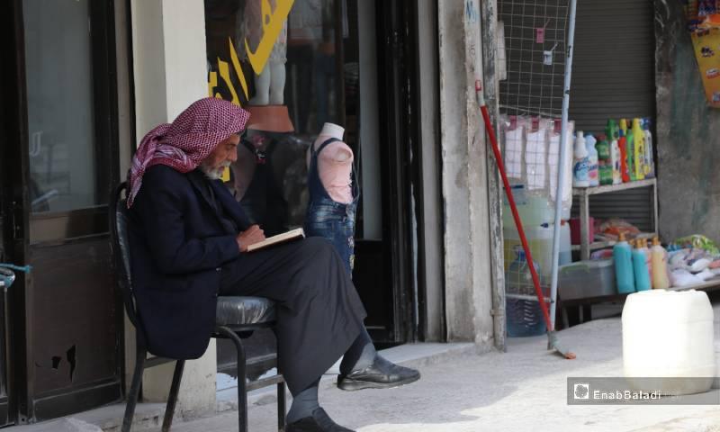 مسن يقرأ القرآن أمام أحد المحلات في أسواق مدينة الباب 4 من أيار 2020 (عنب بلدي)