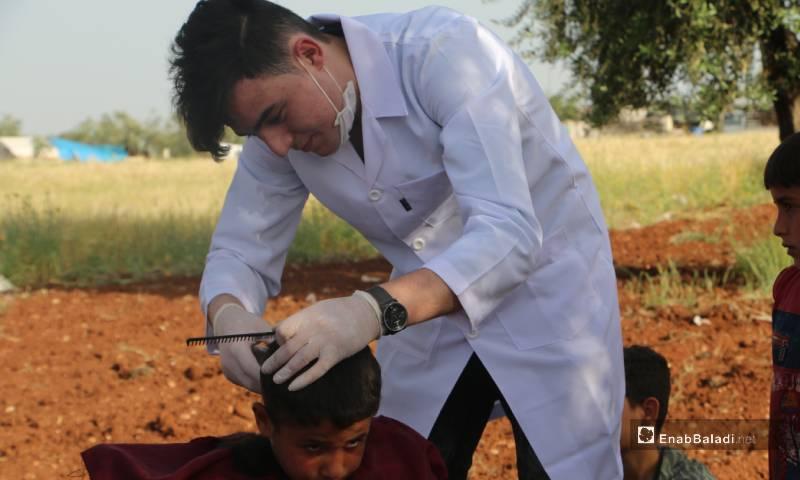 مجموعة حلاقين يتطوعون لحلاقة شعر الأطفال مجانًا داخل مخيمات النزوح في مدينة أعزاز 18 من أيار 2020 (عنب بلدي)