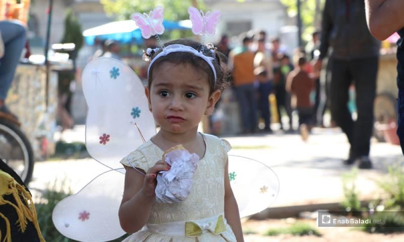 """طفلة تأكل في حديقة """"الشعب"""" وسط مدينة الباب 26 من أيار 2020 (عنب بلدي)"""