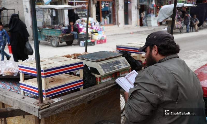 بائع يقرأ القرآن أمام عربته في أحد أسواق مدينة الباب 4 من أيار 2020 (عنب بلدي)