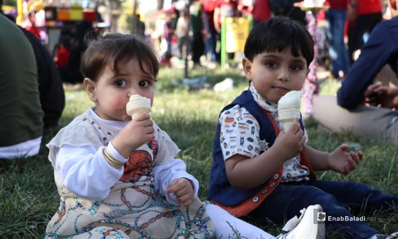"""طفلان يأكلان المثلجات في حديقة """"الشعب"""" وسط مدينة الباب 26 من أيار 2020 (عنب بلدي)"""