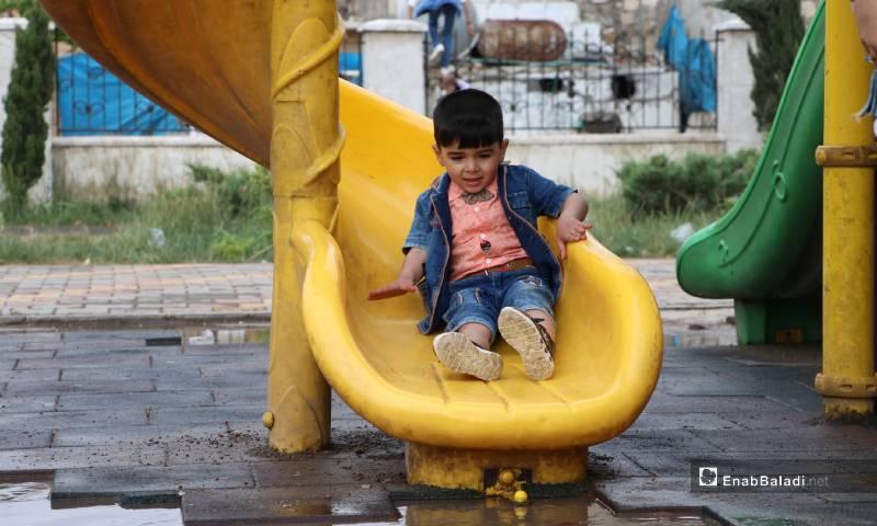 """طفل يلعب في حديقة """"الشعب"""" وسط مدينة الباب 26 من أيار 2020 (عنب بلدي)"""