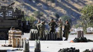 جنود إسرائيليون يقفون بجوار قذائف ووحدة مدفعية متنقلة بالقرب من الجانب الإسرائيلي من الحدود مع سوريا في مرتفعات الجولان التي تحتلها إسرائيل- 26 من آب 2019 (رويترز)
