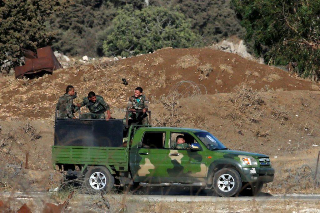 رجال يرتدون الزي العسكري يركبون شاحنة صغيرة في القنيطرة، على الجانب السوري من خط وقف إطلاق النار بين إسرائيل وسوريا، كما يُرى من مرتفعات الجولان التي تحتلها إسرائيل- 26 من تموز 2018 (رويترز).