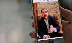 سيدة تشاهد مقطع فيديو على فيس بوك نشره رجل الأعمال السوري رامي مخلوف (AFP)