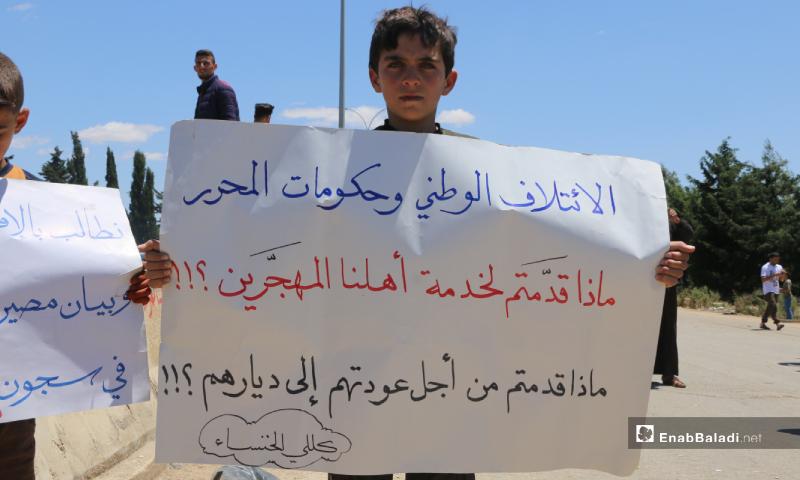 طفل يرفع لافتة في مظاهرة طوفان العودة ثاني أيام عيد الفطر على الطريق الواصل بين إدلب وسرمين - 25 أيار 2020 (عنب بلدي/ أنس الخولي)