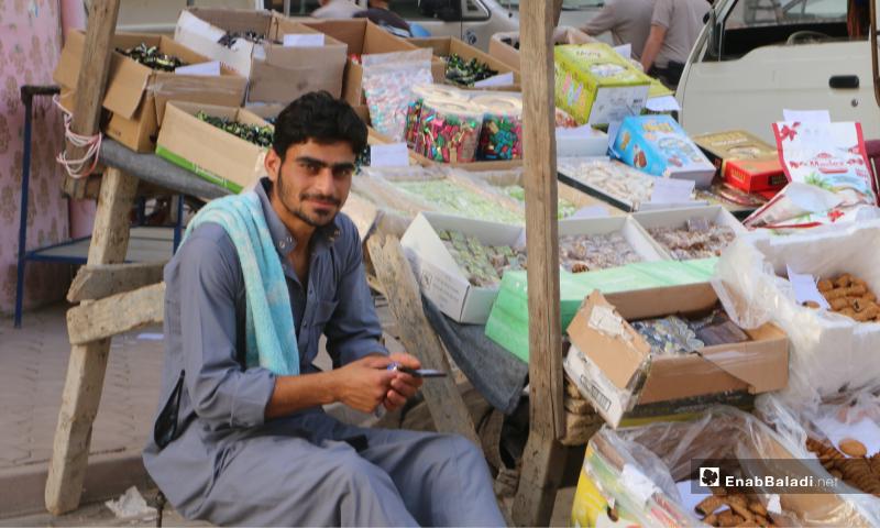 بائع بجوار بسطة لبيع حلويات عيد الفطر في مدينة مارع بريف حلب - 20 أيار 2020 (عنب بلدي/ عبد السلام مجعان)