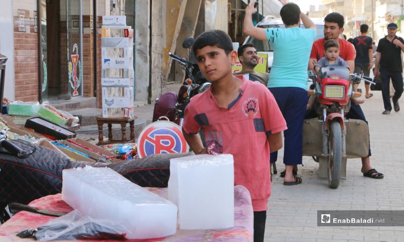 طفل بجوار بسطة لبيع ألواح البوظ، إذ زاد الطلب عليها بعد ارتفاع درجات الحرارة - 20 أيار 2020 (عنب بلدي/ عبد السلام مجعان)