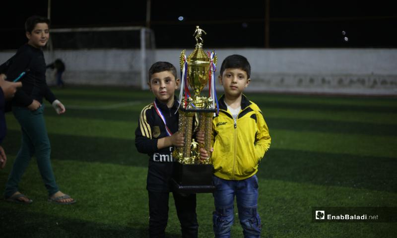 طفلان يحملان كأس بطولة دوري نجوم الشمال بعد انتهاء المباراة النهائية بفوز فريق عقربات على فريق دير حسان في إدلب - 3 أيار 2020 (عنب بلدي)