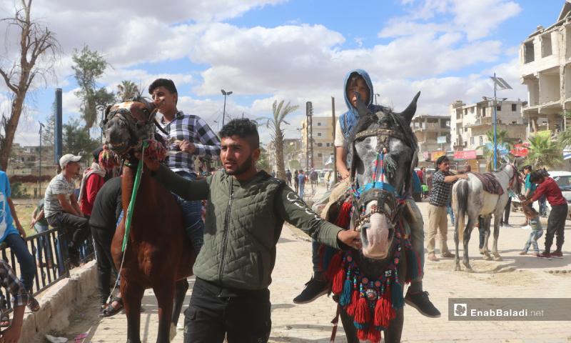 طفلان يركبان على حصانين بمحافظة الرقة شمال شرق سوريا خلال عيد الفطر - 26 أيار 2020 (عنب بلدي)
