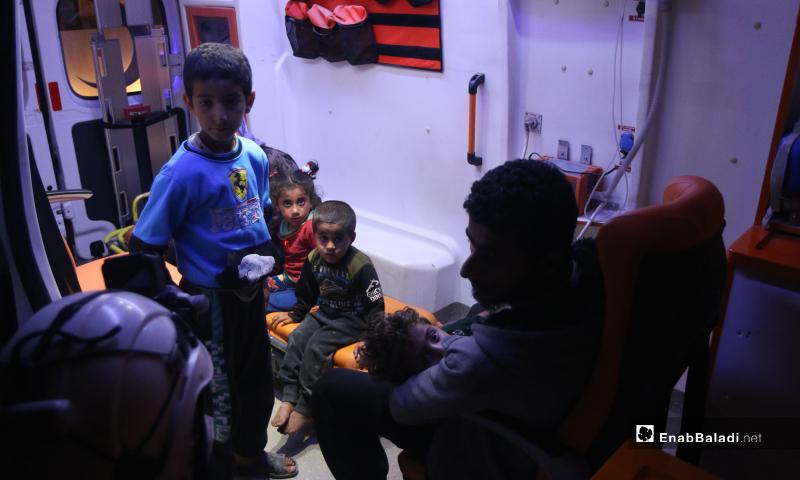 طفل في حضن والده أثناء التوجه إلى قسم الإسعاف مصاب  بتسمم في سيارة إسعاف نتيجة تناول طعام فاسد مقدم من أحد الجمعيات الخيرية في مخيم رعاية الطفولة شمال إدلب - 11 أيار 2020 (عنب بلدي)