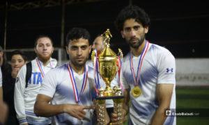 لاعبان يحملان كأس بطولة دوري نجوم الشمال الرابع بعد انتهاء المباراة النهائية بين فريقي عقربات ودير حسان على ملعب قاح في إدلب - 3 أيار 2020 (عنب بلدي)