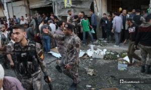 عناصر الشرطة يبعدون الأهالي الذين تجمعوا بالقرب من انفجار عبوة ناسفة في محل خضار بمدينة الباب - 10 أيار 2020 (عنب بلدي)