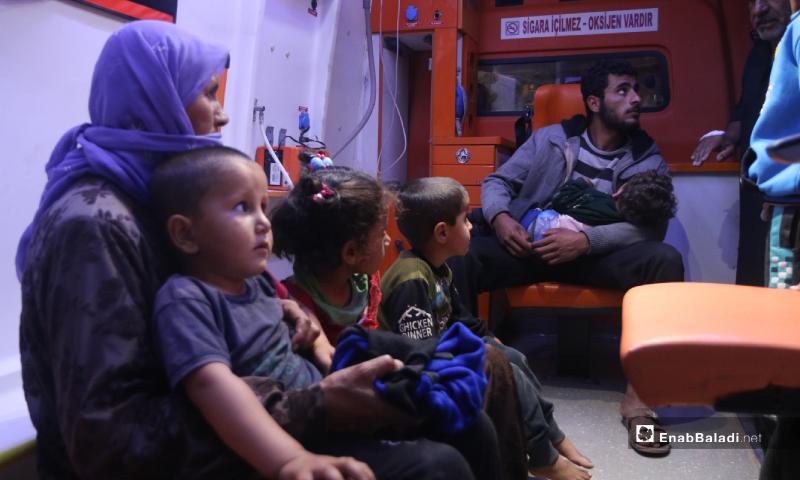 رجل وامرأة يحضنان ابنيهما وبجوارهم أطفال مصابين بتسمم في سيارة إسعاف نتيجة تناول طعام فاسد مقدم من أحد الجمعيات الخيرية في مخيم رعاية الطفولة شمال إدلب - 11 أيار 2020 (عنب بلدي)