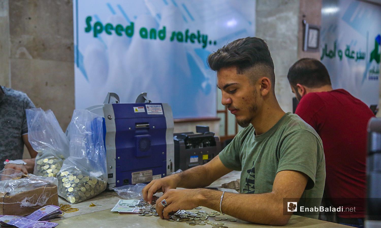 موظف داخل بنك الشام في مدينة إدلب يعمل على تصريف العملة السورية للتركية- 18 حزيران 2020 (عنب بلدي/ يوسف غريبي)