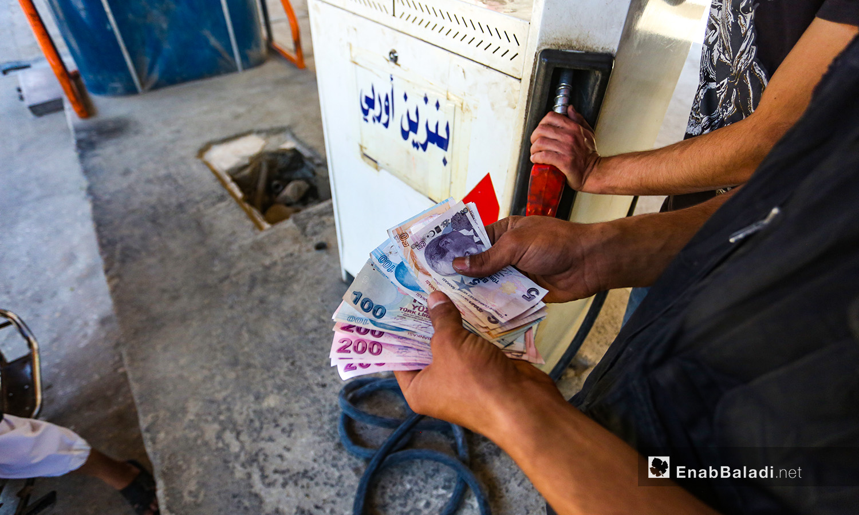 مواطن سوري يتداول العملة التركية في شراء المحروقات داخل مدينة إدلب شمال سوريا- 18 حزيران 2020 (عنب بلدي/ يوسف غريبي)