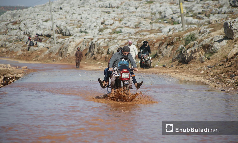 رجلان يحاولان العبور بالدراجة النارية من بركة المياه الناتجة عن العاصفة التي ضربت مخيمات الشمال السوري في كفربني بريف إدلب الشمالي - 19 حزيران 2020 (عنب بلدي/يوسف غريبي)