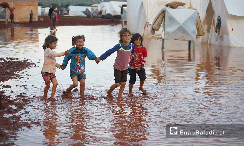 أطفال يلهون في المياه بعد عاصفة مطرية ضربت مخيمات الشمال السوري في كفربني بريف إدلب الشمالي - 19 حزيران 2020 (عنب بلدي/يوسف غريبي)