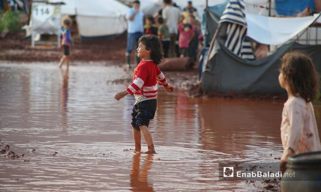 """طفلة تغمر قدماها المياه بعد العاصفة المطرية التي ضربت مخيم """"سهل الخير"""" في كفربني بريف إدلب الشمالي - 19 حزيران 2020 (عنب بلدي/يوسف غريبي)"""