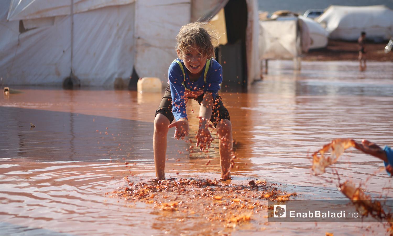 """طفلة تلهو بالماء في مخيم """"سهل الخير"""" بعد العاصفة المطرية في كفربني بريف إدلب الشمالي - 19 حزيران 2020 (عنب بلدي/يوسف غريبي)"""