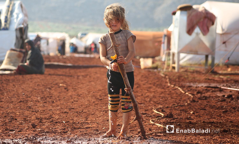 طفلة تلهو بالماء في مخيم سهل الخير بعد العاصفة المطرية في كفربني بريف إدلب الشمالي - 19 حزيران 2020 (عنب بلدي/يوسف غريبي)