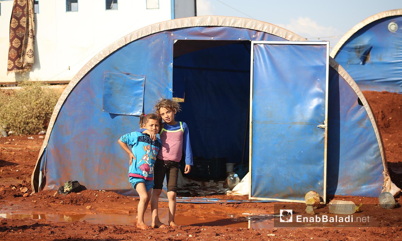 """طفلان أمام خيمتهم في مخيم """"سهل الخير"""" بعد العاصفة المطرية في كفربني بريف إدلب الشمالي - 19 حزيران 2020 (عنب بلدي/يوسف غريبي)"""