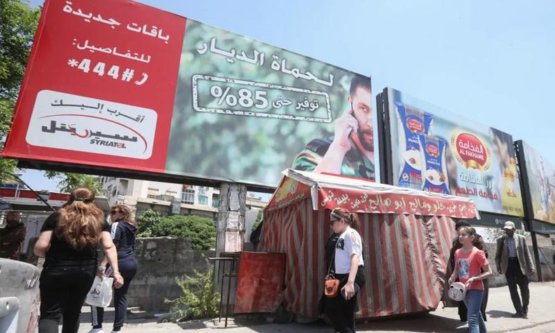 مواطنون يسيرون تحت لوحة إعلانية لأكبر مشغل للهاتف المحمول في سوريا سيريتل المملوك من رامي مخلوف- 11 من أيار 2020 (AFP)