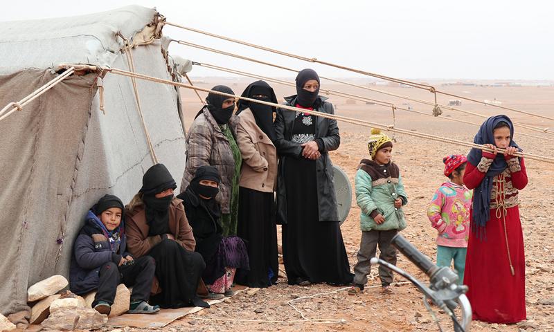 لاجئون سوريون بجوار خيمة في مخيم الركبان على الحدود السورية الأردنية - 1 أيار 2019 (UNHCR)