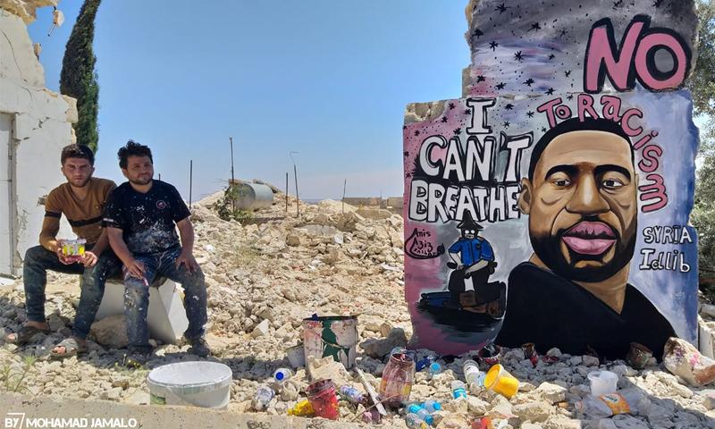 الفنان عزيز أسمر بجانب لوحته الجدارية المتضامنة مع الأمريكي الذي قتل على يد الشرطة خنقًا، جورج فلويد- 1 من حزيران (عزيز أسمر/فيس بوك)