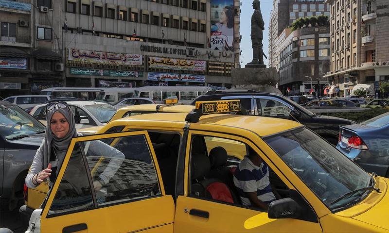 امرأة تغادر سيارة أجرة خلال ساعة الذروة في وسط العاصمة السورية دمشق- 16 من أيلول 2018 (رويترز)