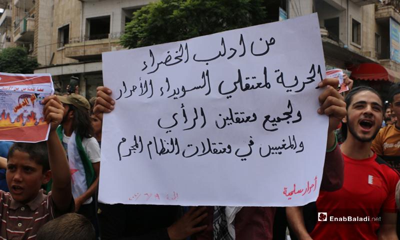 متظاهر في إدلب يرفع لافتة للتضامن مع معتقلي السويداء الأحرار- 19 من حزيران (عنب بلدي/ أنس الخولي)