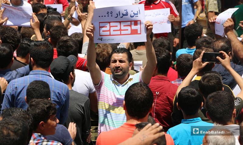 """متظاهر في إدلب يرفع لافتة مكتوب عليها """"أين قرار 2254؟""""- 19 من حزيران (عنب بلدي/ أنس الخولي)"""